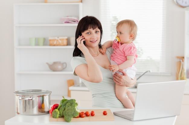 Mulher morena encantadora no telefone enquanto segurava seu bebê em seus braços