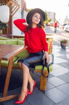 Mulher morena encantadora outono vermelho de malha camisola e saia de couro relaxando no sofá no restaurante de espaço aberto.