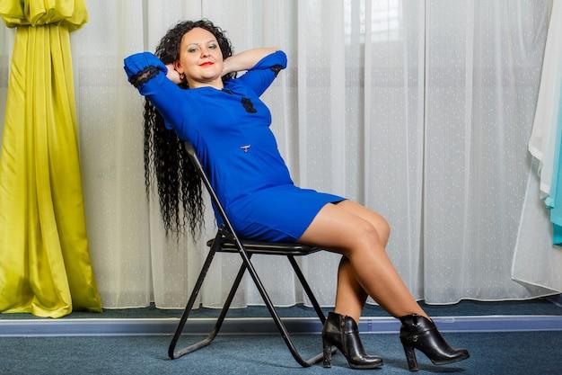 Mulher morena encaracolada de azul se senta em uma cadeira com a cabeça jogada para trás. foto horizontal