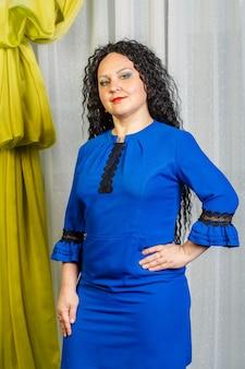 Mulher morena encaracolada em vestido azul posando. foto vertical
