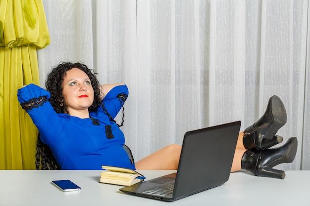 Mulher morena encaracolada está sentada à mesa no escritório com as pernas em cima da mesa. foto horizontal