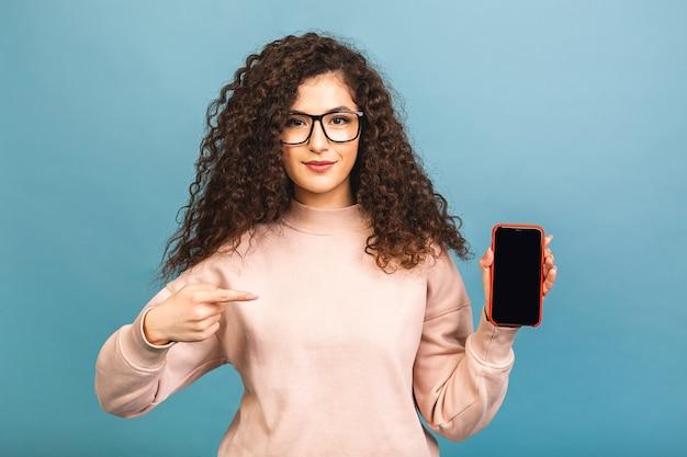 Mulher morena encaracolada feliz surpresa mostrando a tela do smartphone em branco e apontando para ela enquanto olha para a câmera