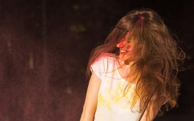 Mulher morena engraçada com cabelo em movimento se divertindo em uma nuvem de pó-de-rosa no festival holi