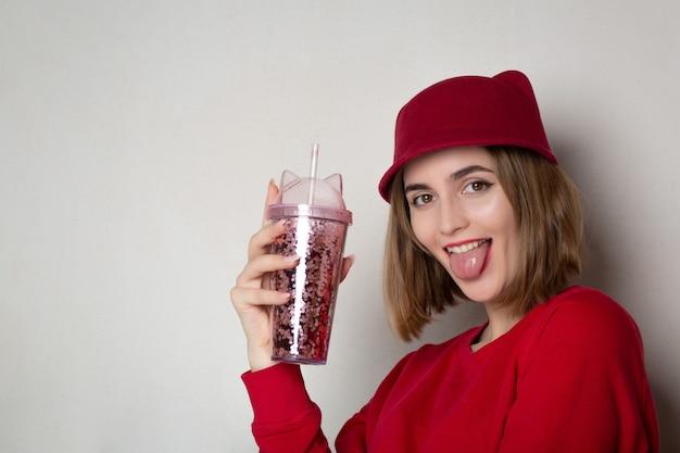 Mulher morena engraçada com chapéu vermelho, segurando o copo de suco de cereja e mostrando a língua. espaço para texto
