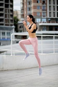 Mulher morena esguia usa roupas esportivas, pulando durante o treino de fitness