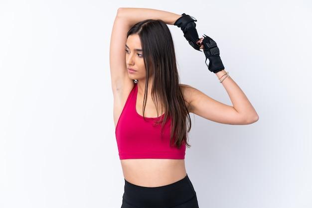 Mulher morena esporte jovem sobre alongamento isolado parede branca
