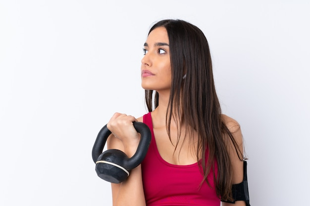 Mulher morena esporte jovem sobre branco fazendo halterofilismo com kettlebell