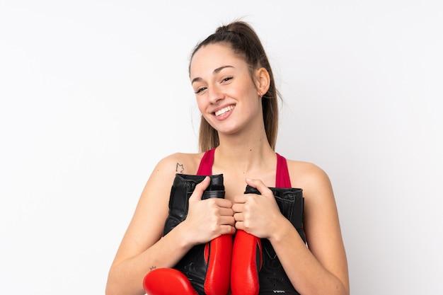 Mulher morena esporte jovem sobre parede branca isolada com luvas de boxe