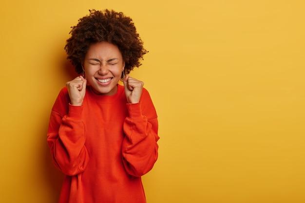 Mulher morena exultante fecha os punhos, comemora a vitória do campeonato, sorri alegremente, vestida com um macacão casual, isolada sobre a parede amarela