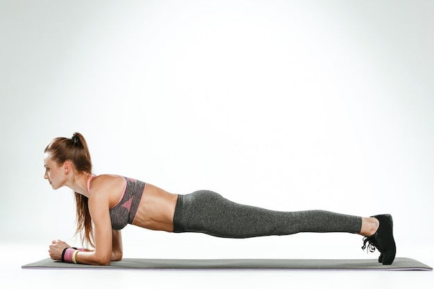 Mulher morena fazendo alguns exercícios de alongamento em uma academia