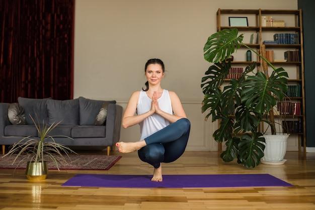 Mulher morena feliz com um top e legging fazendo poses de ioga equilibrada no tapete em um quarto em casa