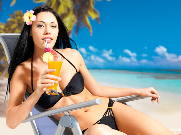 Mulher morena feliz de férias bebendo suco de laranja na praia