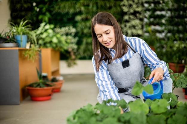 Mulher morena feliz derramando água doce em vasos de plantas cultivadas em jardim doméstico