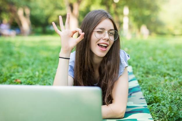 Mulher morena feliz em óculos deitada na grama no parque com um computador laptop e mostrando sinal de ok