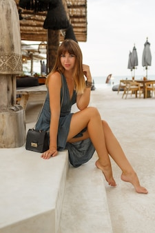 Mulher morena feliz em um vestido sexy, posando em um elegante restaurante de praia no estilo \ bali. toda a extensão.