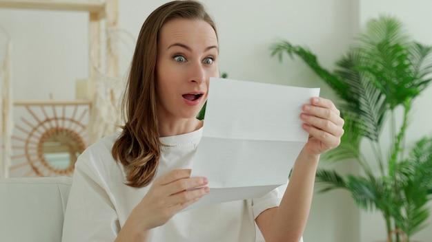 Mulher morena feliz lendo boas notícias em carta, extrato bancário.