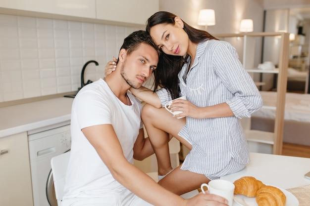Mulher morena feliz passando a manhã com o namorado bonito e sorrindo