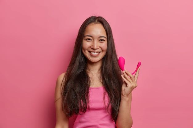 Mulher morena feliz posa com vibrador bluetooth inteligente, usa app especial no celular para melhorar o orgasmo, segura a ferramenta de sexo para aumentar o prazer, isolada na parede rosa. tecnologias modernas e vida sexual