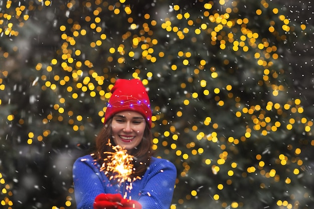 Mulher morena feliz se divertindo com luzes cintilantes na rua durante a queda de neve. espaço para texto