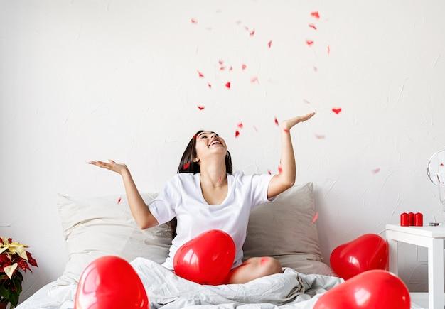 Mulher morena feliz sentada na cama com balões em forma de coração vermelho jogando confete para o alto