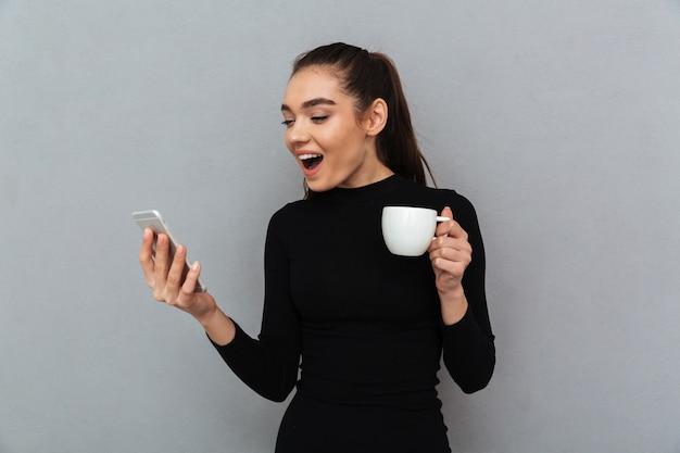 Mulher morena feliz surpresa em roupas pretas, olhando para o smartphone