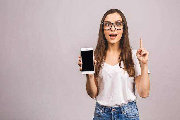 Mulher morena feliz surpresa mostrando a tela do smartphone em branco enquanto com a boca aberta