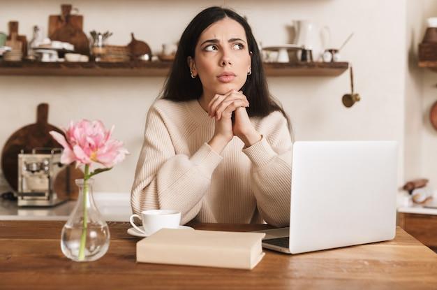 Mulher morena feliz tomando café e usando o laptop na cozinha de casa