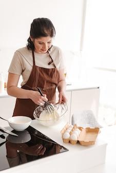 Mulher morena feliz usando avental, cozinhando na cozinha de casa e amassando massa com batedeira manual