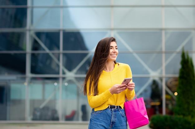 Mulher morena feliz vestida de suéter amarelo, com sacolas de compras e celular desfrutando de compras.