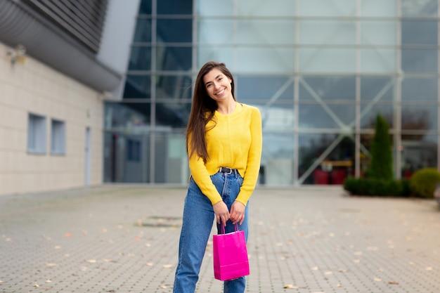 Mulher morena feliz vestida de suéter amarelo, com sacos de compras, desfrutando de compras. compras, conceito de estilo de vida