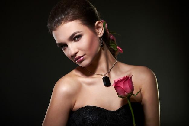 Mulher morena feminina atraente com rosa no estúdio