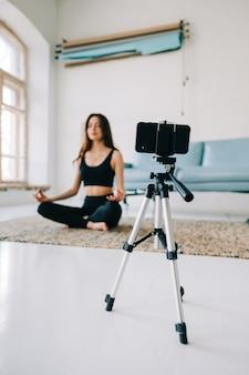 Mulher morena fitness meditando na frente da câmera no tripé, fazendo ioga em casa