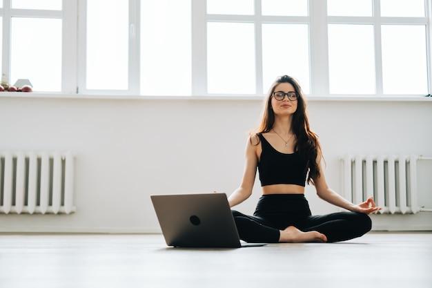 Mulher morena fitness meditando na frente do laptop, fazendo ioga dentro de casa, em casa