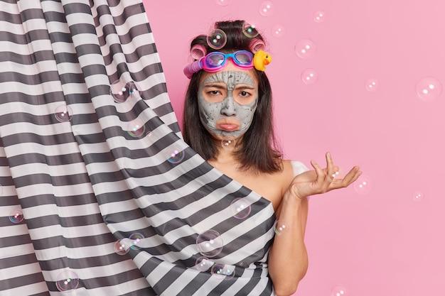 Mulher morena fofa descontente passa por procedimentos de beleza no banheiro, bolsa lábio inferior olha infeliz para a câmera aplica máscara de argila e bobes de cabelo posam atrás da cortina do chuveiro ao redor de bolhas
