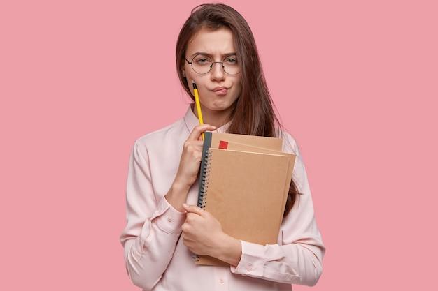 Mulher morena frustrada tem uma expressão facial séria, segura um lápis e um bloco de notas, franze a testa, pensa em escrever papel de diploma