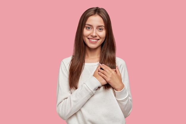 Mulher morena generosa e satisfeita com sorriso terno, mantém as duas mãos no peito
