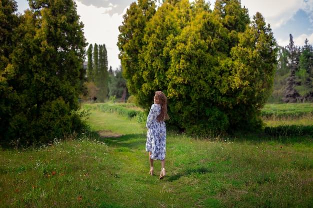 Mulher morena glamour de salto alto andando em vestido longo com estampa de flores no parque