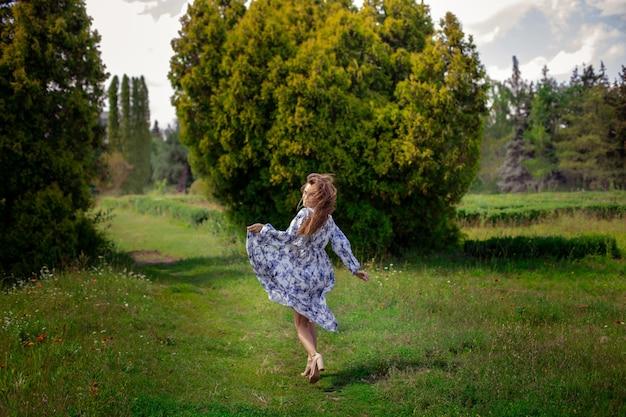 Mulher morena glamour de salto alto corre em vestido longo com estampa de flores no parque