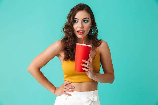 Mulher morena glamourosa usando brincos de moda, beber bebida ou refrigerante de palha e copo de papel vermelho grande