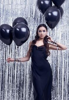 Mulher morena hispânica elegante em vestido preto luxuoso detém balões
