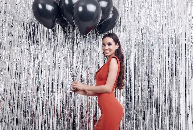 Mulher morena hispânica elegante vestido vermelho luxuoso detém balões