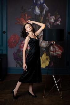 Mulher morena incrível com vestido de seda preta posando em um quarto de designer com um abajur