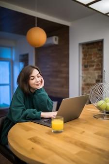 Mulher morena interessada está trabalhando em seu laptop na mesa da cozinha, bebendo suco de laranja