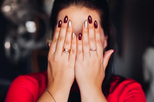 Mulher morena irreconhecível, escondendo o rosto com as mãos.