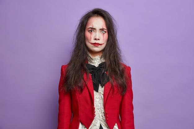 Mulher morena irritada e descontente com a imagem de um monstro assustador celebra o festival de outubro e o dia das bruxas usa poses profissionais de maquiagem assustadora contra a parede roxa