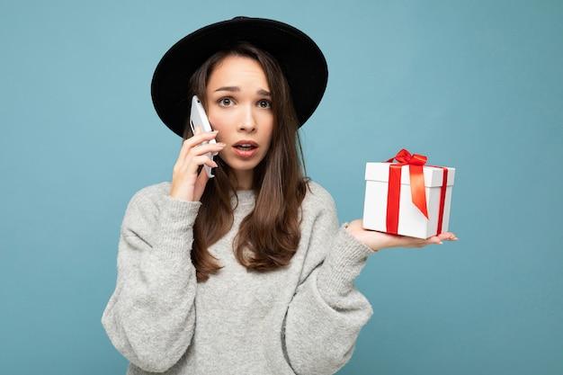 Mulher morena isolada sobre a parede de fundo azul, usando elegante chapéu preto e suéter cinza segurando uma caixa de presente, falando no smartphone e olhando para a câmera.
