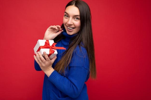 Mulher morena isolada sobre a parede de fundo vermelho, vestindo uma blusa casual azul, segurando uma caixa de presente branca com fita vermelha e olhando para a câmera.