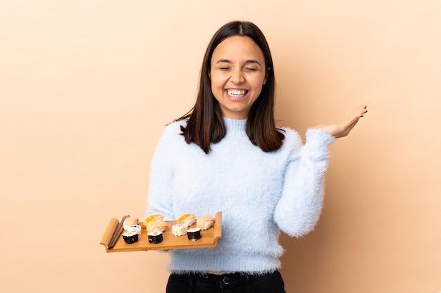 Mulher morena jovem de raça mista, segurando o sushi sobre parede isolada, sorrindo muito
