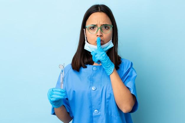Mulher morena jovem dentista de raça mista segurando ferramentas sobre parede, apontando para o lado e fazendo o gesto de silêncio
