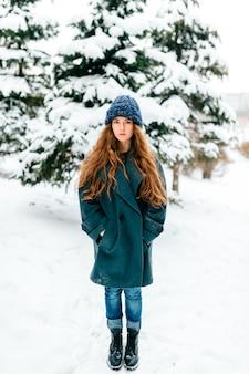 Mulher morena jovem e bonita elegante posando no parque de inverno nevado.
